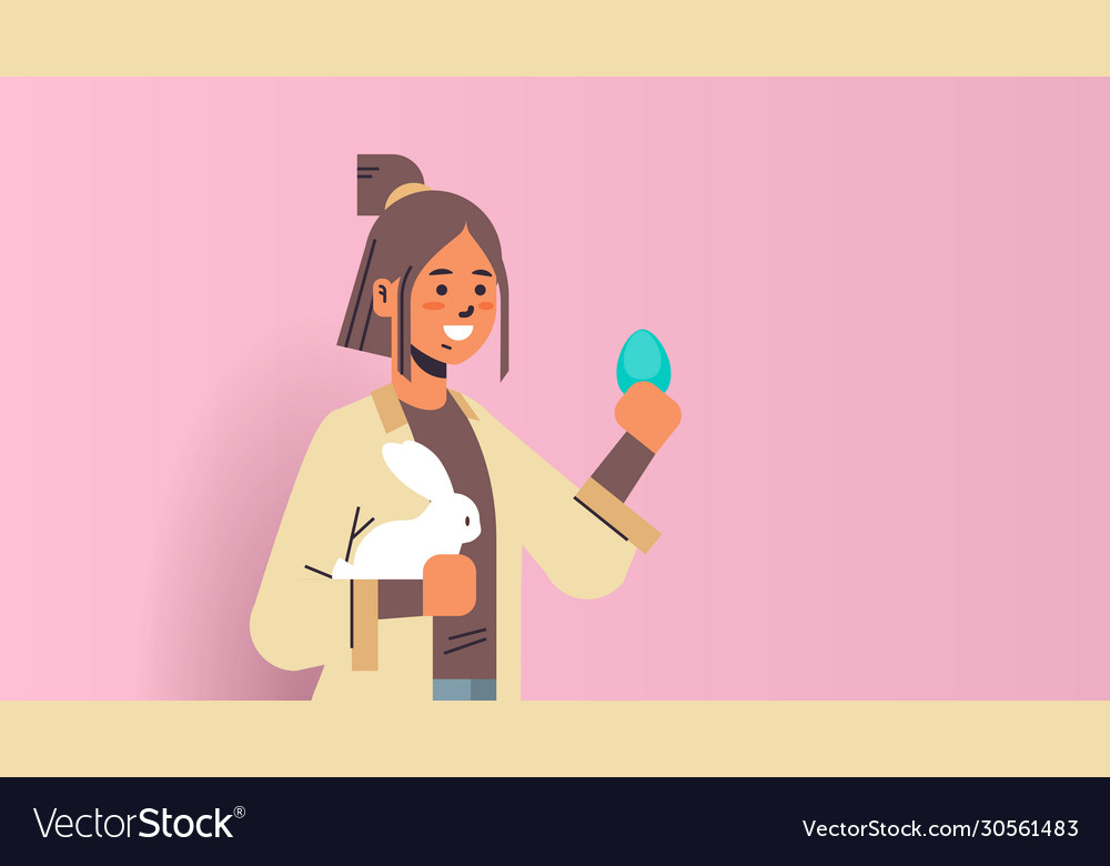 Attractive woman holding rabbit and egg smiling