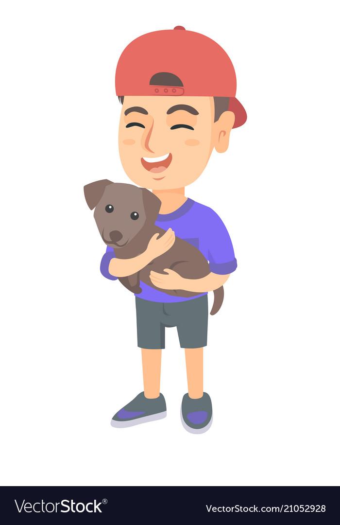 Caucasian happy boy in a cap holding a dog