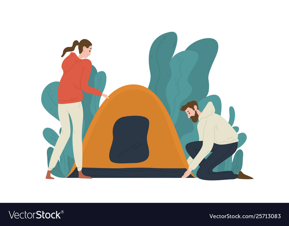 Young couple setting up tent on campsite pair of