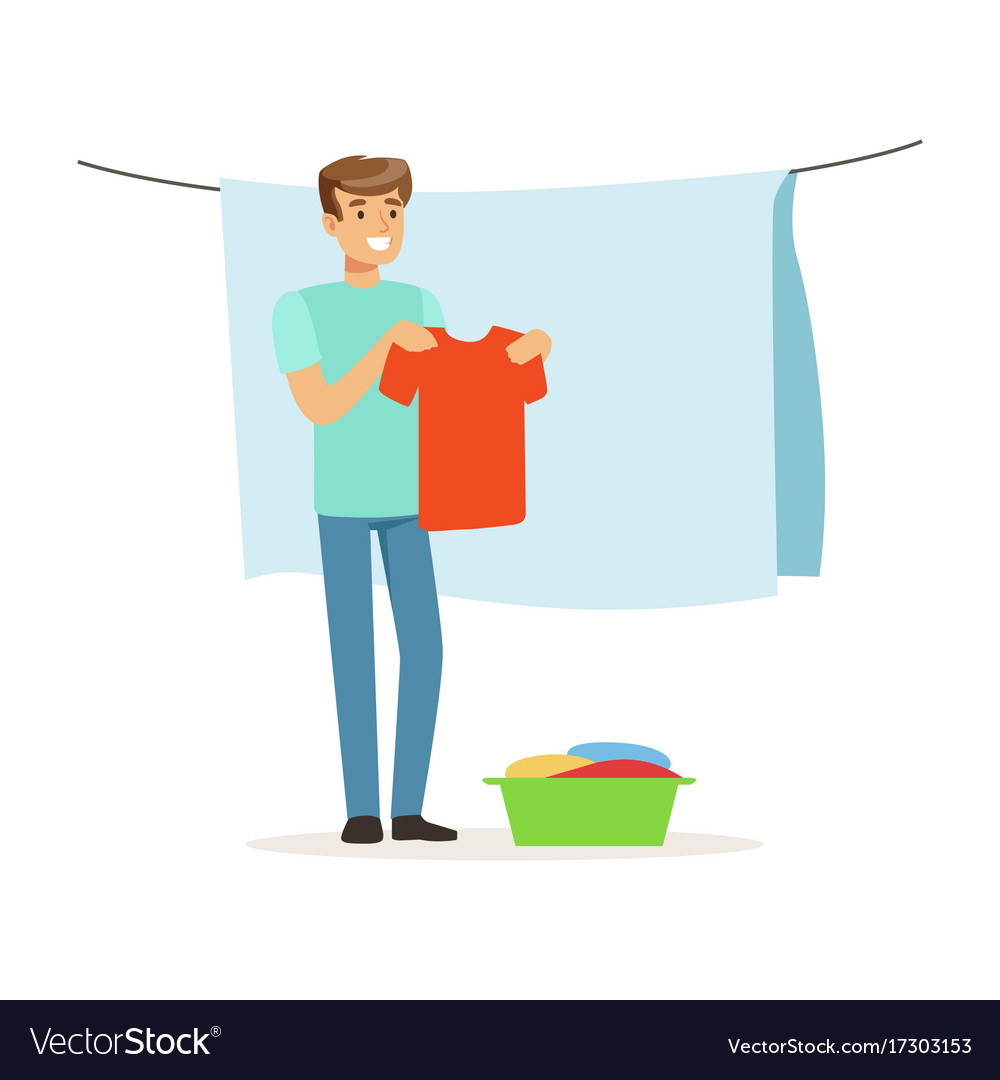Young smiling man hanging wet clothes out to dry