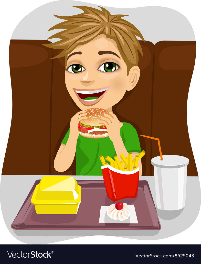 Young boy eating cheeseburger with french fries