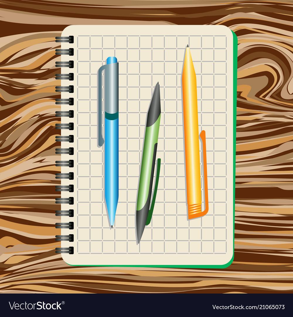 Notebook blue pen green pen and yellow pen
