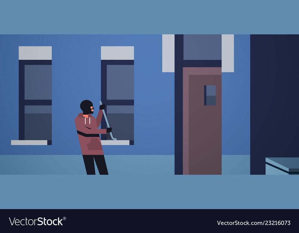 Burglar in black mask using crowbar breaking