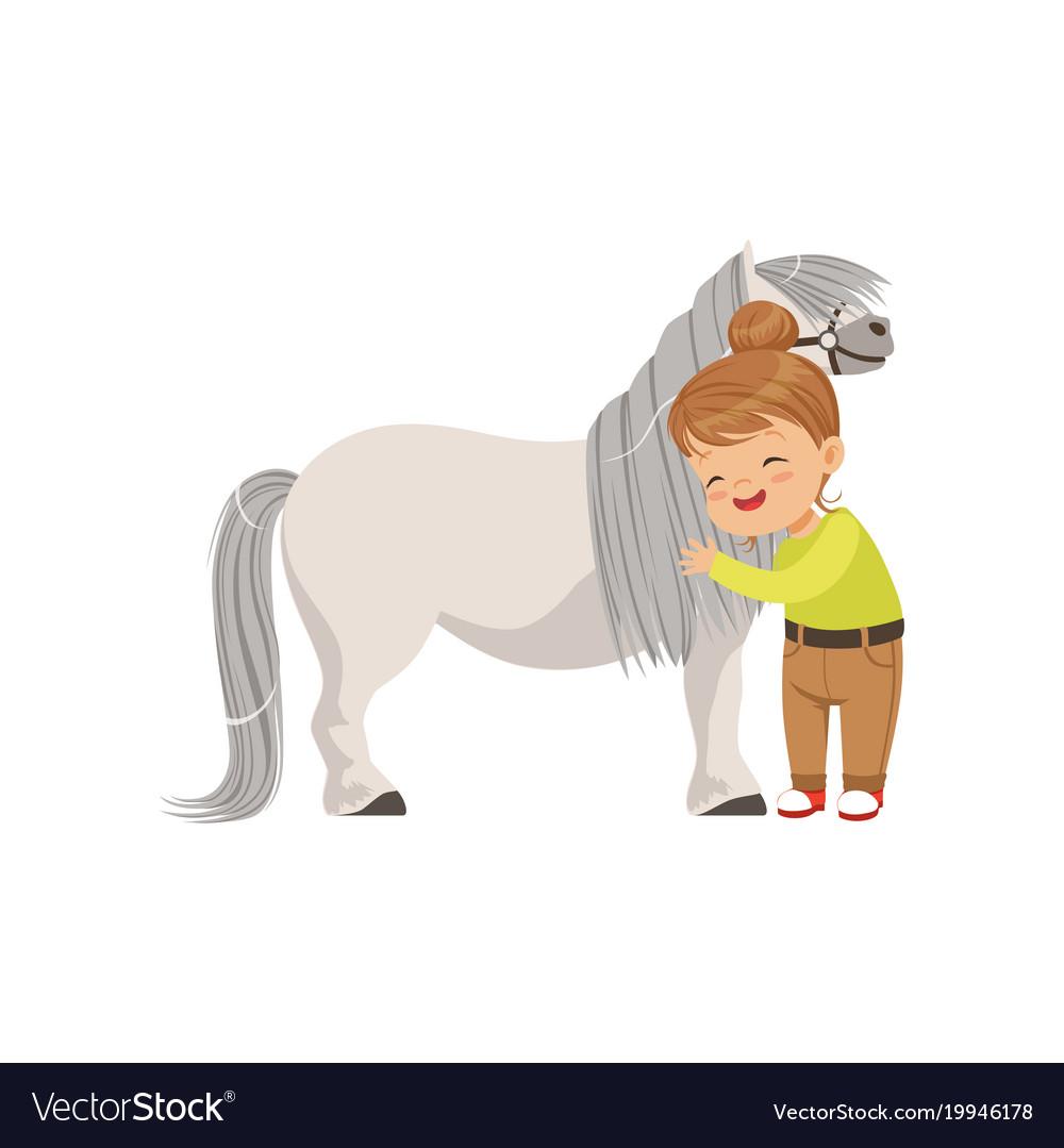 Lovely little girl hugging pony horse kid taking