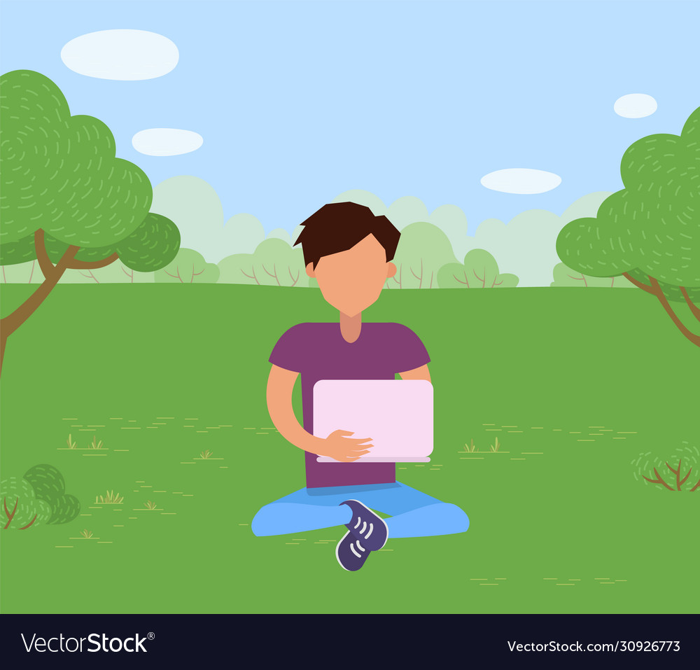 Man sitting on grass in park with laptop