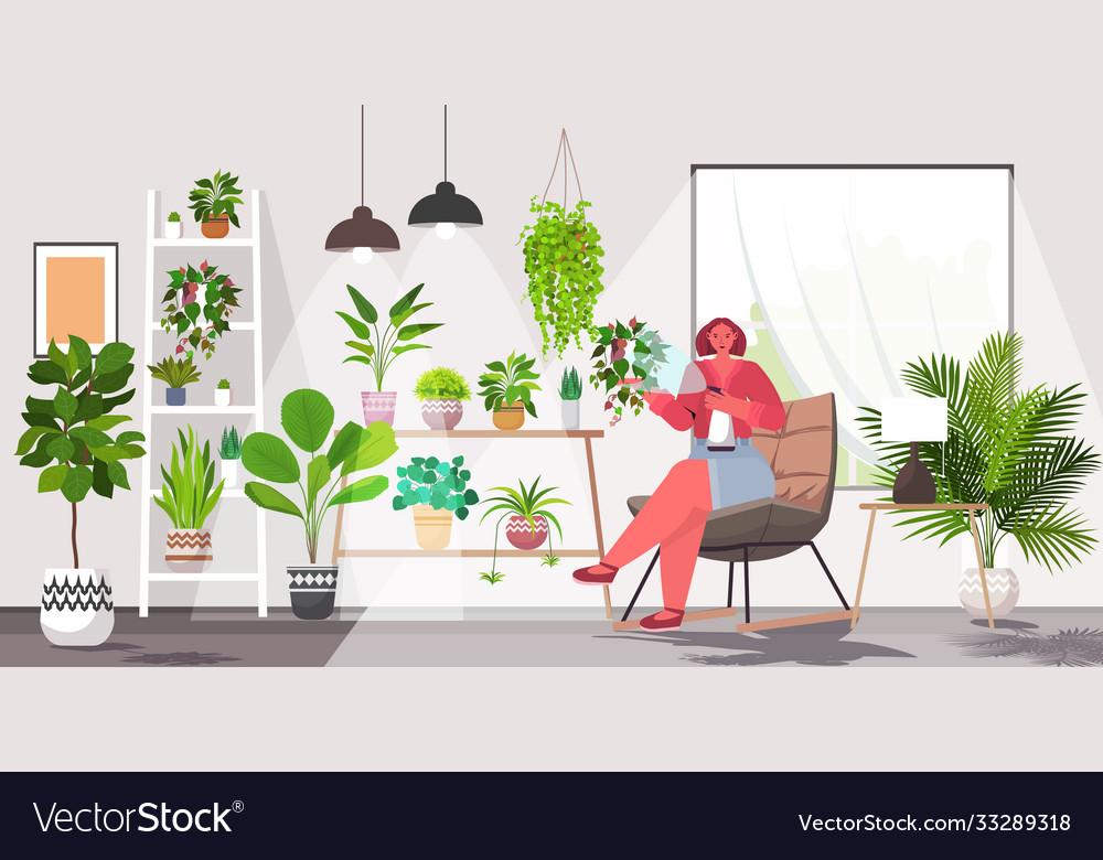 Woman taking care houseplants living room