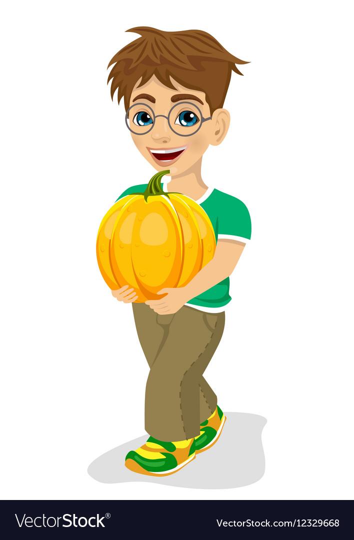 Cute little boy carrying a large pumpkin smiling