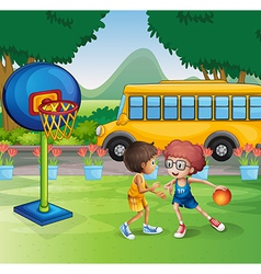 Two boys playing basketball near the school bus vector image vector image