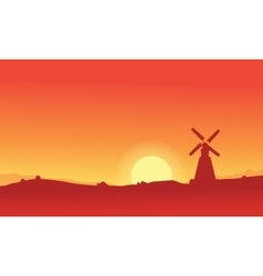 Silhouette of windmill on orange backgrounds vector