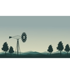 Silhouette of windmill and tree scenery vector