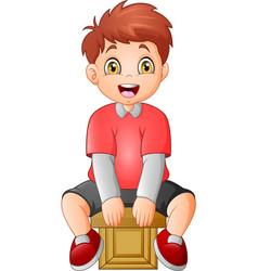 cute little boy sitting on a cube vector image
