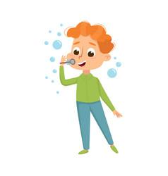 Cute redhead boy blowing soap bubbles through wand vector