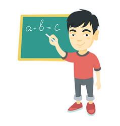 Asian schoolboy writing on the blackboard vector