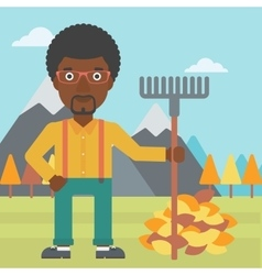 Man with rake standing near heap of autumn leaves vector image