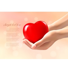 Hands holding a red heart vector