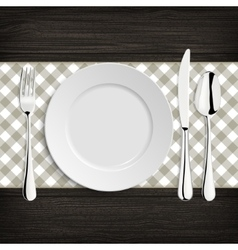 Plate with spoon khife and fork on a wood table vector image