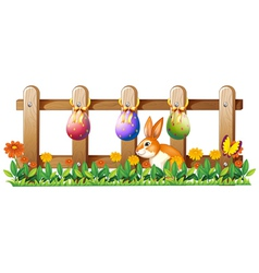 Easter eggs at the fence and a bunny vector image vector image