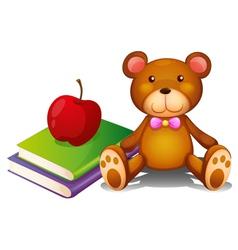 An apple above the books and a huggable bear vector image