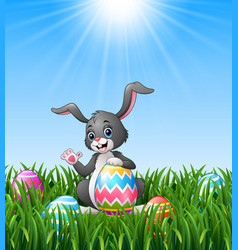 Cartoon bunny waving hand with holding easter egg vector