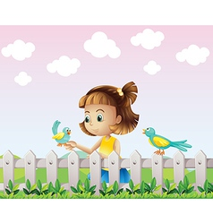 A young girl playing with the birds near the fence vector