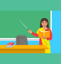 Indian teacher with book near blackboard in class vector