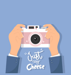 Hand holding camera with just say cheese vector