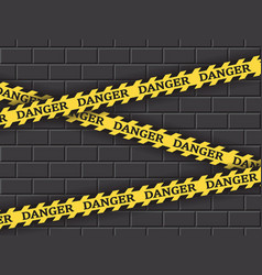 Restrictive yellow tape danger against a brick vector