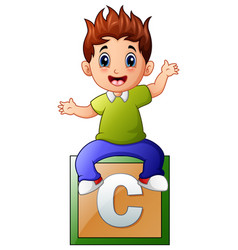little boy sitting on alphabet cube vector image