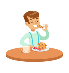 Happy boy sitting at the table and eating cookies vector