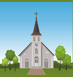 Church standing on a lawn surrounded by trees vector