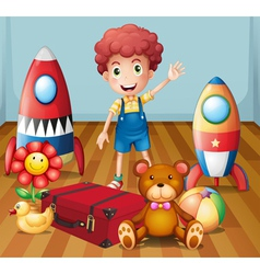 A young boy with his toys inside the room vector
