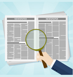 Hand holding a magnifying glass on business news vector