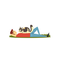 Young man lying on the grass cat sitting on it vector
