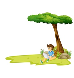 A boy using his laptop under a tree vector image vector image