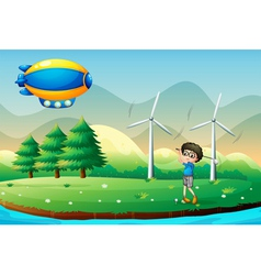 A boy playing golf in the field with windmills vector image vector image