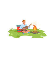 young man playing guitar sitting next to bonfire vector image
