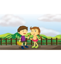 A young girl and a young boy at the wooden bridge vector