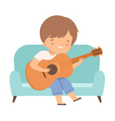 cute boy sitting on sofa and playing guitar kids vector image