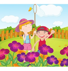 Kids catching butterflies at the garden vector image