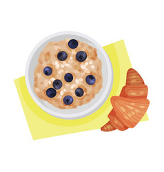 Bowl oatmeal porridge and blueberries served vector