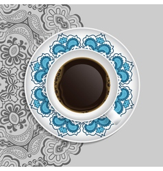 Cup of coffee and decorative ornament on a saucer vector