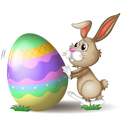 A bunny pushing an easter egg vector image