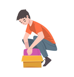 Young man squatting and packing cardboard box vector