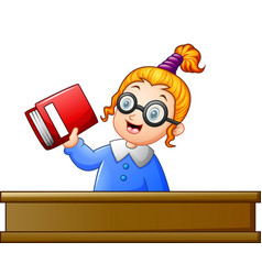 school girl holding textbook at desk vector image