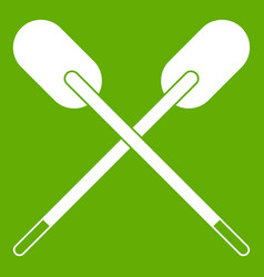 Two wooden crossed oars icon green vector