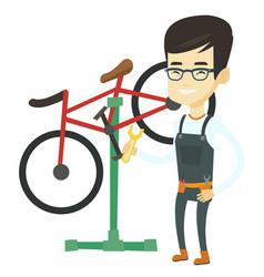 Asian bicycle mechanic working in repair shop vector
