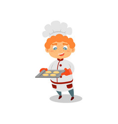 cute red-haired boy holding tray with fresh-baked vector image