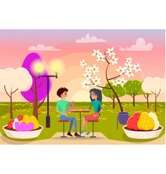 Couple in love sits at table on sunset in park vector