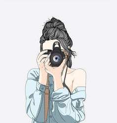 A woman holds a stylish camera and wears vector