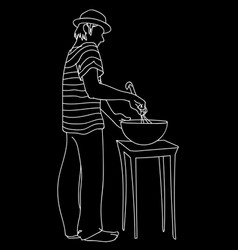 young man in hat and striped t-shirt prepares food vector image